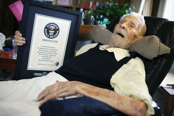 111-year-old Alexander Imich holds Guinness World Records certificate recognizing him as world's oldest living man during interview with Reuters at home in New York City