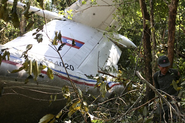 A rescue worker makes his way past the wreckage of an air force plane at its crash site near Nadee village, in Xiang Khouang province