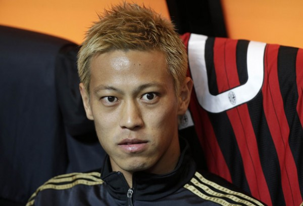 AC Milan's Honda looks on as he sits on the bench before the Italian Serie A soccer match against Inter Milan at San Siro stadium in Milan