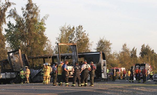 Rescue workers, police and firefighters survey the scene where a truck and a tour bus collided near Orland