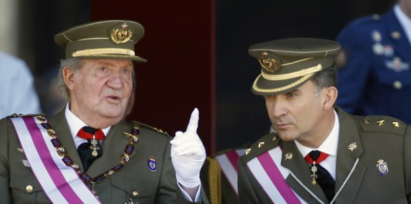 Spain's Crown Prince Felipe listens to his father King Juan Carlos during a ceremony at the Monastery of San Lorenzo de El Escorial outside Madrid