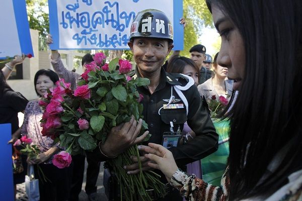 A soldier receives flowers from members of a pro-army group that came to a barrack in central Bangkok