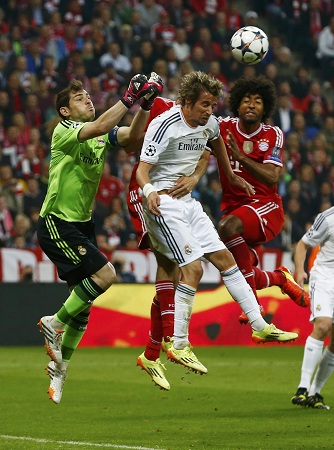 Bayern Munich's Dante challenges Real Madrid's goalkeeper Casillas and team mate Coentraoduring their Champions League semi-final second leg soccer match in Munich