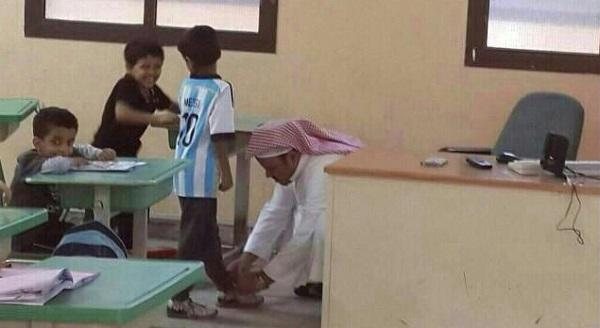 معلم يربط حذاء طالب داخل الفصل