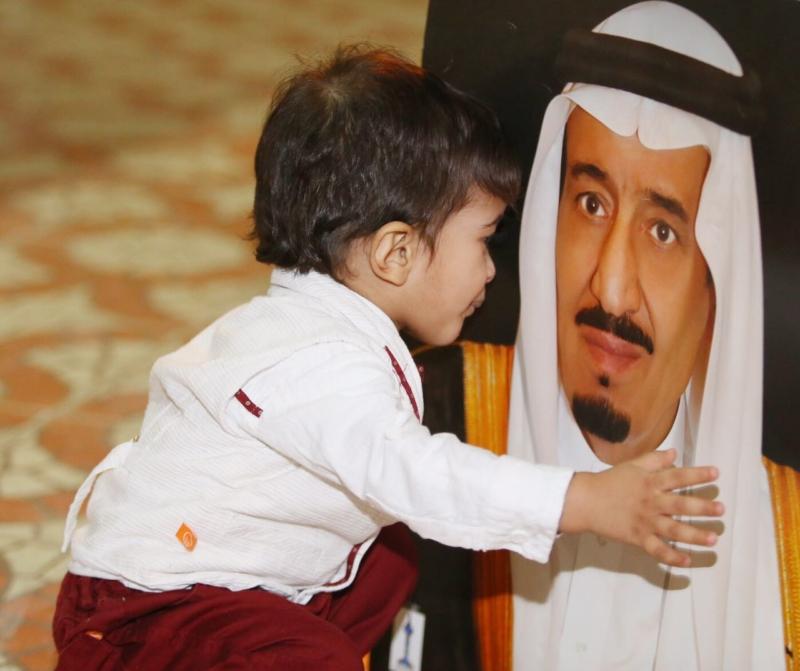 طفل يقبل صورة الملك