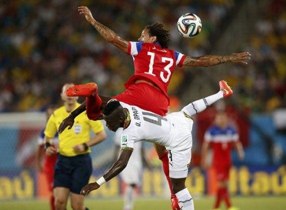 Jermaine Jones of the U.S. jumps for the ball against Ghana's Daniel Opare during their 2014 World Cup Group G soccer match at the Dunas arena in Natal