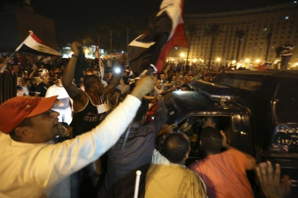 Supporters of Sisi greet police officers while they celebrate at Tahrir square in Cairo