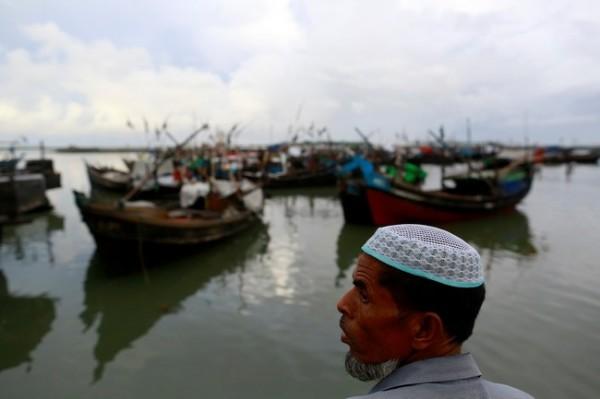A Rohingya Muslim stands near a jetty outside Sittwe