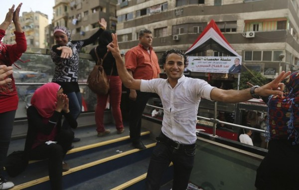 """Members of the """"Egyptian National Movement Party"""" and supporters of the army and police dance to traditional songs as they ask people to go vote in Cairo"""
