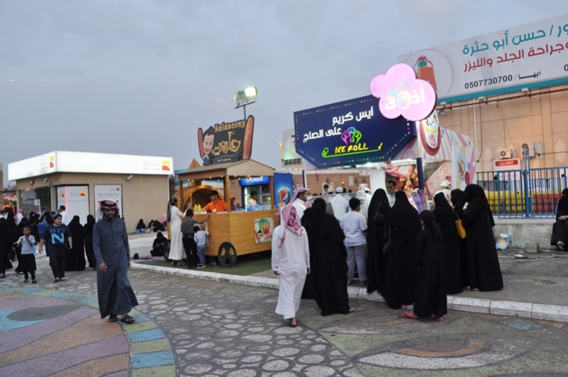 صور لشباب سعوديين يعملون بمهرجان ابها