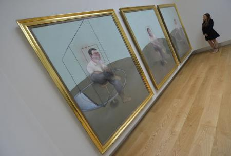 A Christie's employee poses as she views 'Three Studies for a Portrait of John Edwards' by British artist Francis Bacon at Christie's auction house in central London